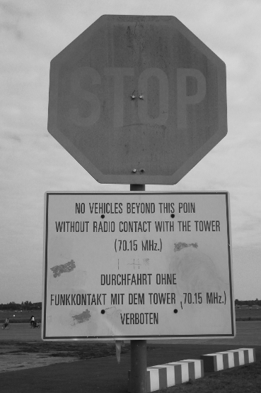 Verwittertes Stoppschild mit Angabe der Tower-Funkfrequenz